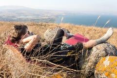 Giovane donna che si trova indietro nell'alta vista del lago Kineret dell'erba Fotografie Stock