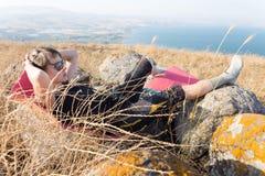 Giovane donna che si trova indietro nell'alta vista del lago Kineret dell'erba Fotografia Stock Libera da Diritti