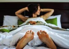 Giovane donna che si trova a letto e che sveglia Immagine Stock
