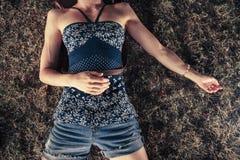 Giovane donna che si trova nell'erba Fotografia Stock
