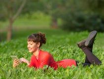 Giovane donna che si trova nell'erba con la compressa digitale Fotografie Stock