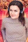 Giovane donna che si trova su una coperta in un parco di autunno e che ascolta il Th Immagini Stock Libere da Diritti