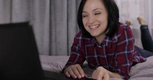 Giovane donna che si trova sul letto e che ha video chiacchierata facendo uso del webcam sul computer portatile stock footage