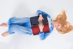 Giovane donna che si trova sul pavimento in suoi pigiami con un computer portatile Immagini Stock Libere da Diritti