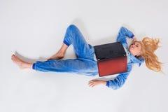 Giovane donna che si trova sul pavimento in suoi pigiami con un computer portatile Fotografia Stock Libera da Diritti