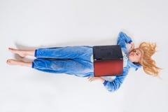 Giovane donna che si trova sul pavimento in suoi pigiami con un computer portatile Fotografia Stock