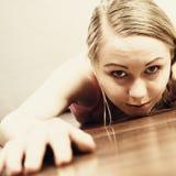 Giovane donna che si trova sul primo piano del fronte di pavimento Fotografie Stock