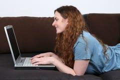 Giovane donna che si trova sul sofà e che per mezzo del suo computer portatile immagini stock libere da diritti