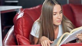 Giovane donna che si trova sul sofà e sul libro di lettura a casa archivi video