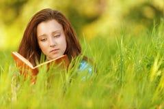 Giovane donna che si trova sull'erba Fotografia Stock