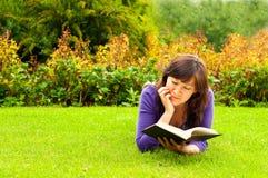 Giovane donna che si trova sull'erba e che legge un libro Fotografie Stock Libere da Diritti