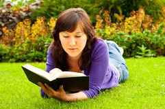 Giovane donna che si trova sull'erba e che legge un libro Immagine Stock