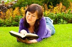 Giovane donna che si trova sull'erba e che legge un libro Immagine Stock Libera da Diritti