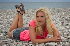 Giovane donna che si trova sulla spiaggia della ciottolo-pietra Immagini Stock