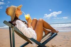 Giovane donna che si trova sulla spiaggia e che rinfresca con il succo Fotografia Stock