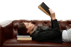 Giovane donna che si trova sullo strato con i libri sotto la sua testa Immagini Stock