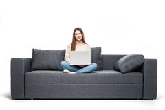 Giovane donna che si trova sullo strato e che per mezzo del computer portatile a casa Immagini Stock Libere da Diritti