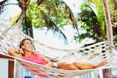 Giovane donna che si trova in un'amaca vicino ad una spiaggia Fotografia Stock Libera da Diritti