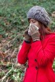 Giovane donna che soffre da un freddo, da un'influenza o dalle allergie soffianti il suo naso Fotografie Stock Libere da Diritti