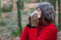 Giovane donna che soffre da un freddo, da un'influenza o dalle allergie soffianti il suo naso Immagini Stock