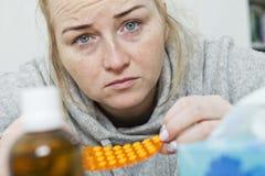 Giovane donna che soffre dall'emicrania a casa immagine stock
