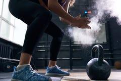Giovane donna che solleva Kettlebells nella palestra di CrossFit Immagine Stock