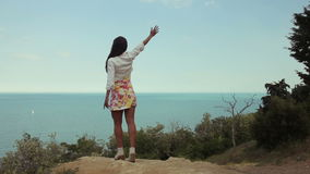 Giovane donna che solleva le mani all'oceano stock footage