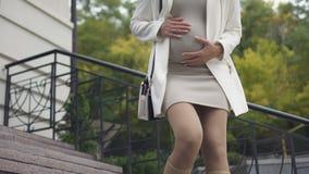 Giovane donna che sopporta dolore acuto improvviso di sensibilità del bambino all'aperto, contrazioni stock footage