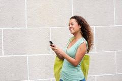 Giovane donna che sorride all'aperto con il telefono cellulare Immagine Stock