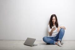Giovane donna che sorride con il telefono cellulare e le cuffie, sedentesi vicino Fotografia Stock