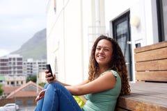 Giovane donna che sorride con il telefono cellulare nella città Fotografia Stock