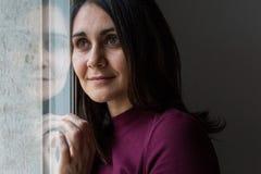 Giovane donna che sorride dalla finestra Fotografia Stock Libera da Diritti