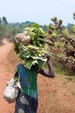 Giovane donna che sostiene gli oneri gravosi sulla sua testa Immagini Stock