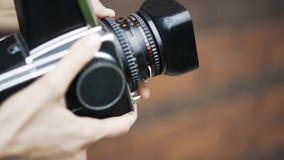 Giovane donna che spara una coppia con una macchina fotografica antiquata stock footage