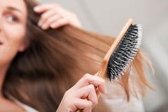 Giovane donna che spazzola i suoi capelli Immagini Stock Libere da Diritti
