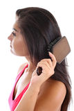 Giovane donna che spazzola i suoi capelli Immagine Stock