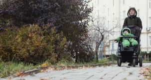 Giovane donna che spinge carrozzina archivi video