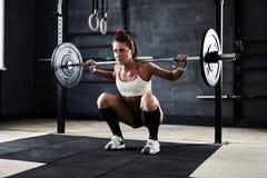 Giovane donna che spinge i pesi Fotografia Stock Libera da Diritti