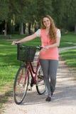 Giovane donna che sta accanto alla sua bici Fotografie Stock