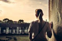 Giovane donna che sta al bordo di costruzione e che esamina vista durante il tramonto attraverso la finestra antica con lo spazio Fotografia Stock Libera da Diritti