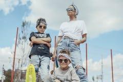 Giovane donna che sta con i suoi figli al campo da giuoco Concetto 'nucleo familiare' felice immagine stock libera da diritti