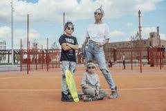 Giovane donna che sta con i suoi figli al campo da giuoco Concetto 'nucleo familiare' felice immagine stock