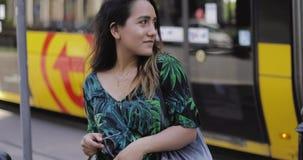 Giovane donna che sta davanti ad un tram della via stock footage