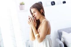 Giovane donna che sta di mattina davanti alla finestra Fotografia Stock Libera da Diritti