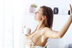 Giovane donna che sta di mattina davanti alla finestra Immagine Stock