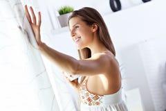 Giovane donna che sta di mattina davanti alla finestra Immagini Stock Libere da Diritti