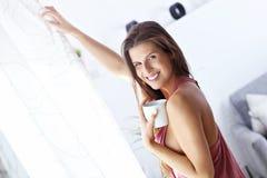 Giovane donna che sta di mattina davanti alla finestra Fotografia Stock