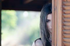 Giovane donna che sta dietro di una finestra Fotografia Stock