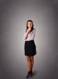 Giovane donna che sta e che pensa con lo spazio della copia Fotografia Stock