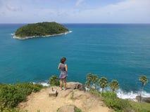 Giovane donna che sta su una scogliera con seaview ad un'isola, sul punto di vista di Rawai dell'isola di Phuket Immagine Stock Libera da Diritti